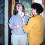 A friend pins a corsage on Lynn at April's baby shower